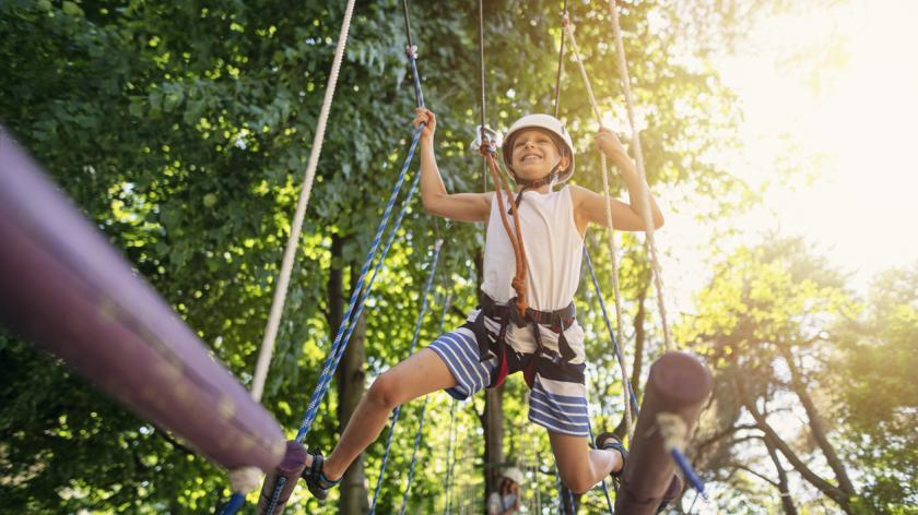 A boy walking in ropes course in adventure park