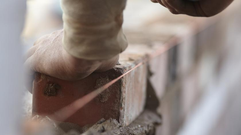 A bricklayer works on a new domestic kitchen extension using reclaimed bricks.