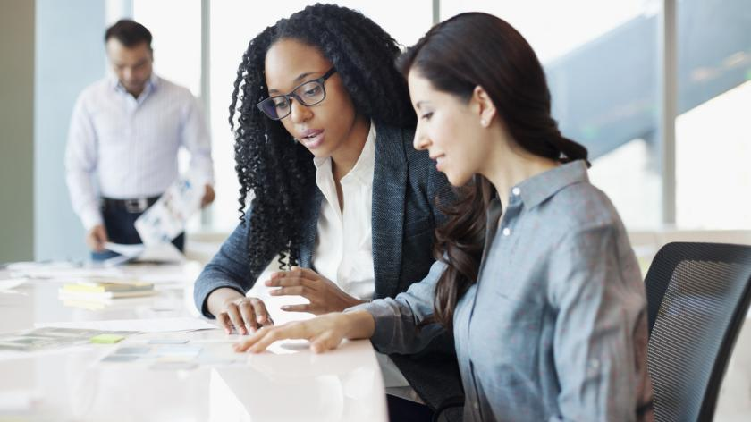 Two women coordinating ideas and strategy in bright sunny open office meeting conference room.