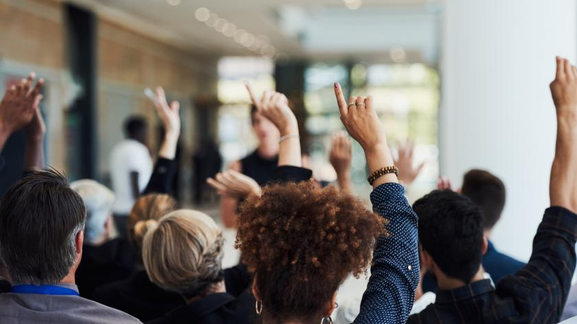 Shot of a group of businesspeople raising their hands to ask questions during a conference.