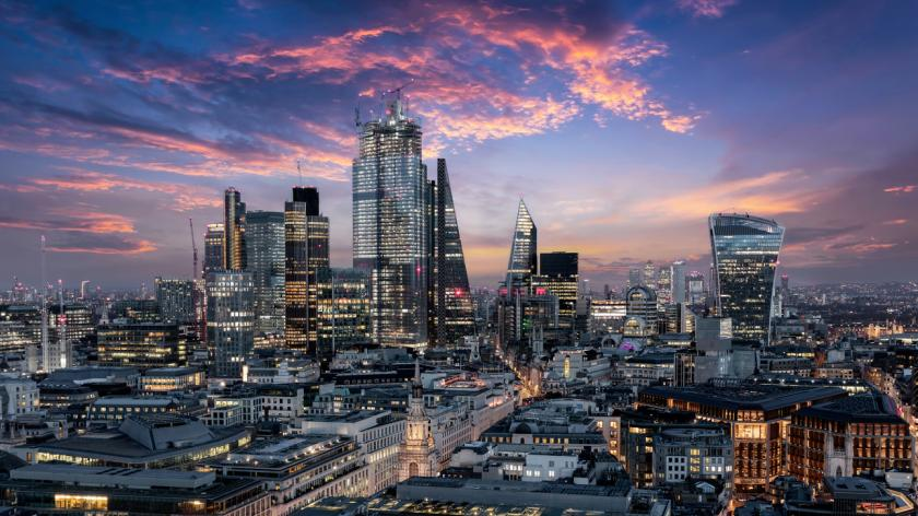 UK fintech review: The City of London, financial district of the Metropole, just after sunset with illuminated buildings and cloudy sky, United Kingdom
