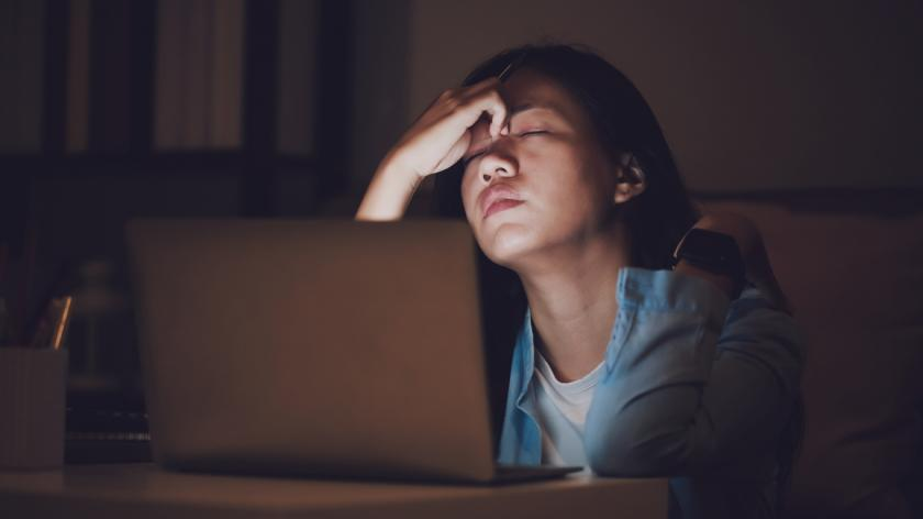 Businesswoman with Zoom fatigue working late at night. Concentrated and feel sleepy at the desk in dark room with laptop or notebook.Concept of people workhard and burnout syndrome.