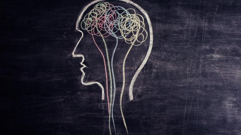 Brain made of multicolored lines drawn on chalkboard