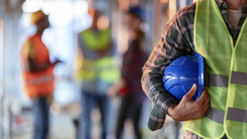 A builder holding a blue helmet