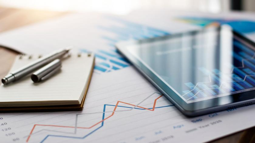 Business document report on paper and tablet with sales data and financial business growth graph.