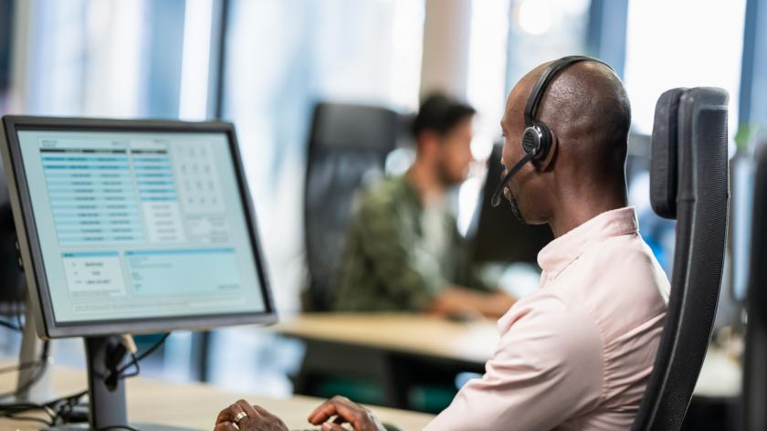 Secretary using a computer and talking to a customer over a headset while doing customer support in a call centre.
