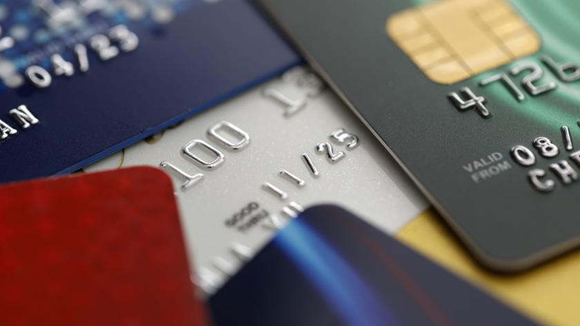 Loan charge voluntary restitution: Part two. stack of multicolored credit cards on black background