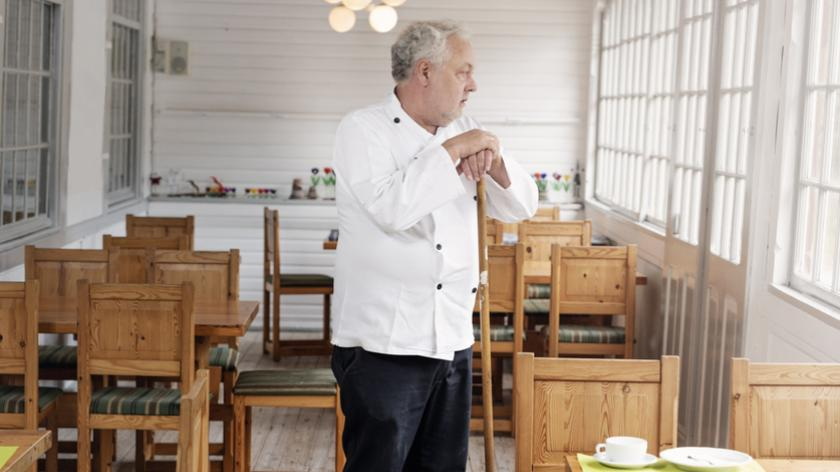 Restaurant owner wearing his chef's whites standing in his empty restaurant.