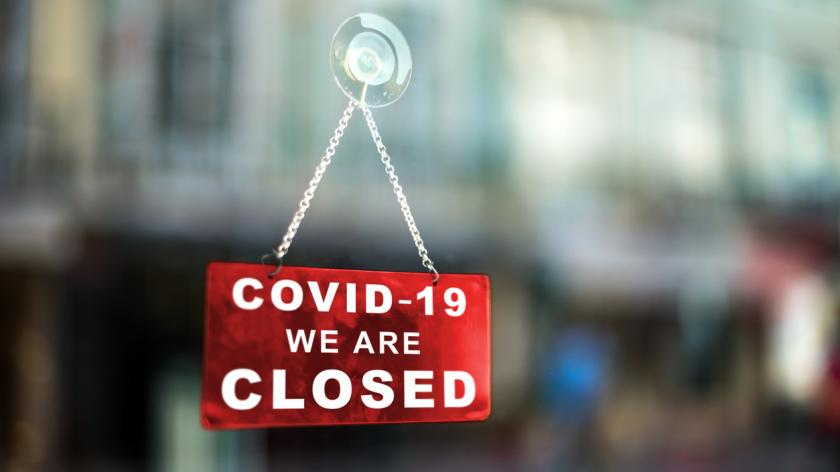 Red sign on window informing that the business is closed due to covid-19