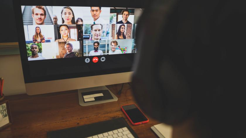 Man working at home having a video conference with colleagues.