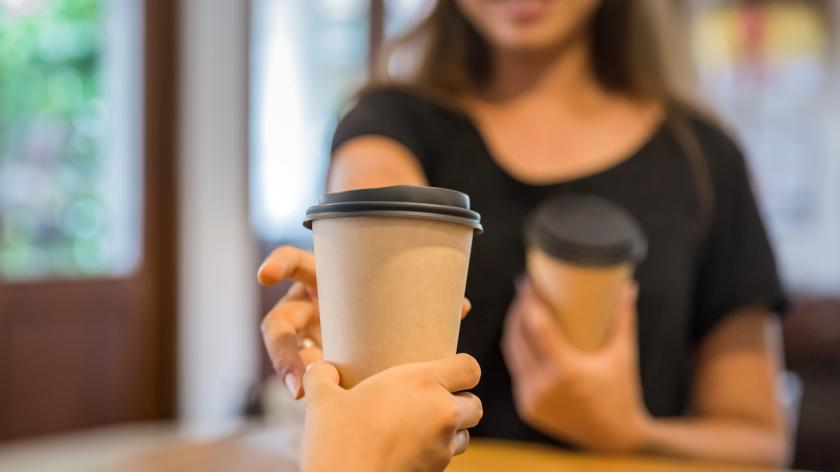 A woman picking up takeaway coffee from barista