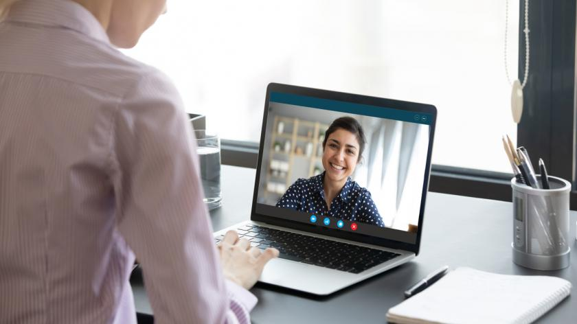 Indian girl communicate with friend on-line by video call, pc screen view over female shoulder. Mental health expert online therapy, colleagues work on common project use videoconferencing app concept.