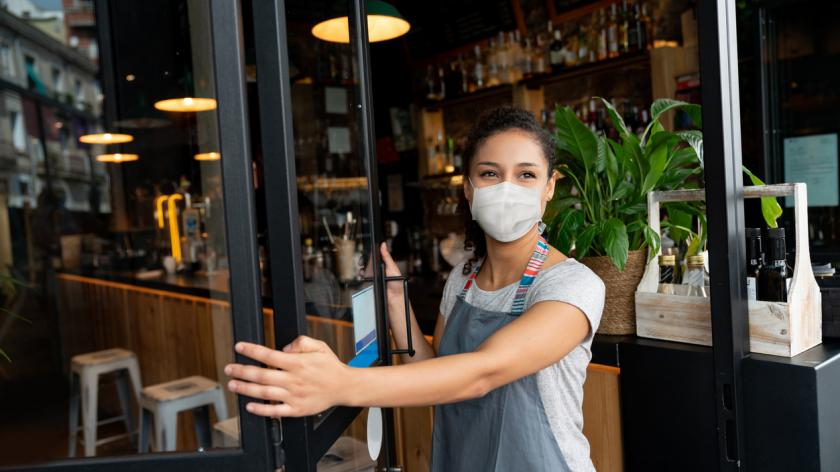 business owner opening the door at a cafe wearing a facemask