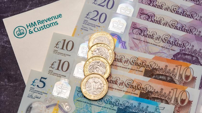 HMRC tax form with UK banknotes and coins