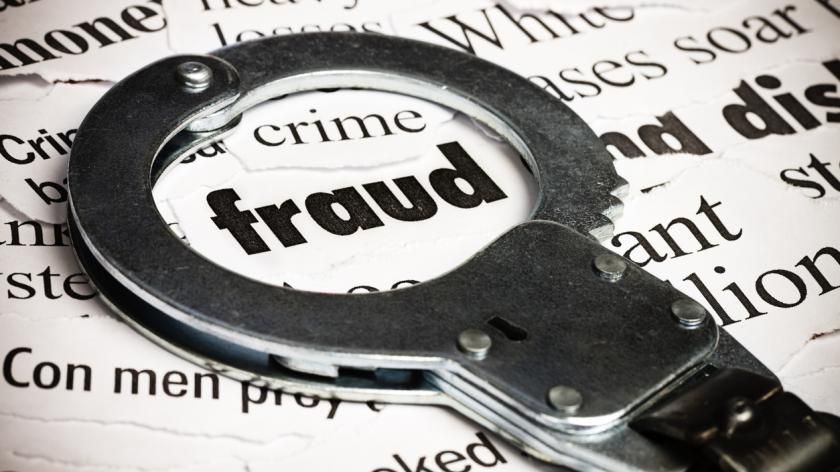 Handcuffs over newspaper with the word fraud