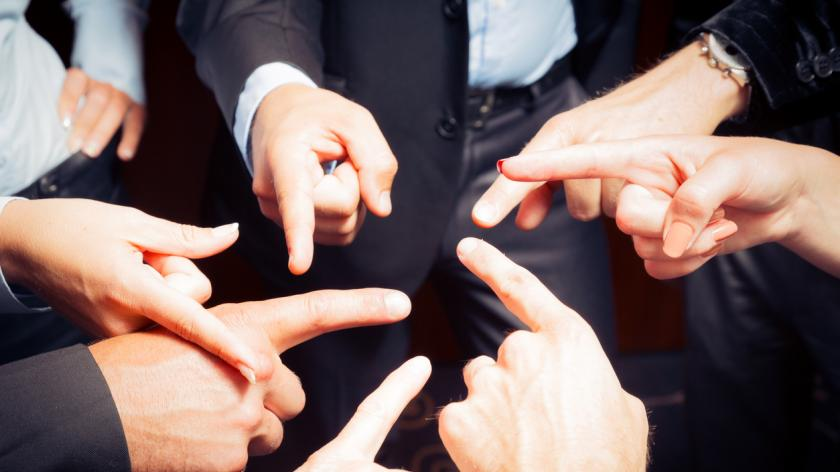 Business team pointing at each other