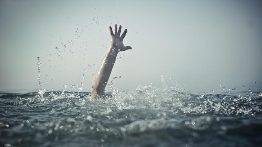 Hand reaching out of deep water, focus on water splash