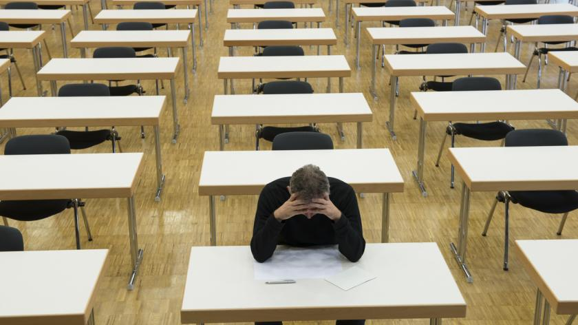Single person in an examination hall. Sitting at thinking in front of a white sheet of paper. Concept for failure, knowledge, learning, loneliness or the looser.