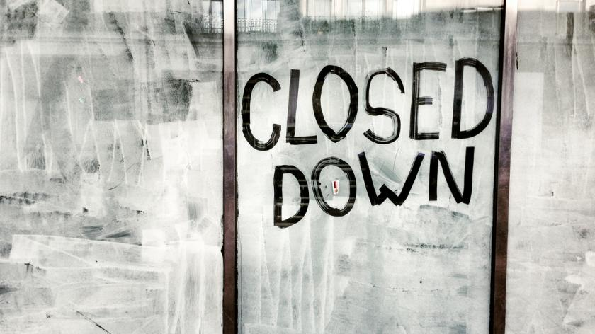An empty retail unit with 'CLOSED DOWN' written on the window.