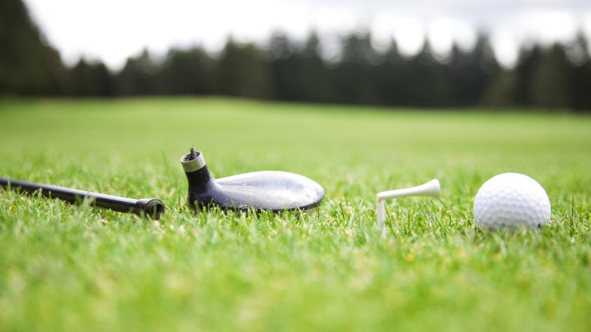 Broken golf driver and tee with the golf ball next to them on a golf course
