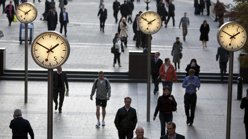 Pedestrians walking past clocks in Canary Wharf