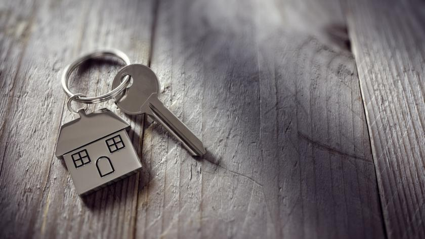 A picture of a house key on a keychain
