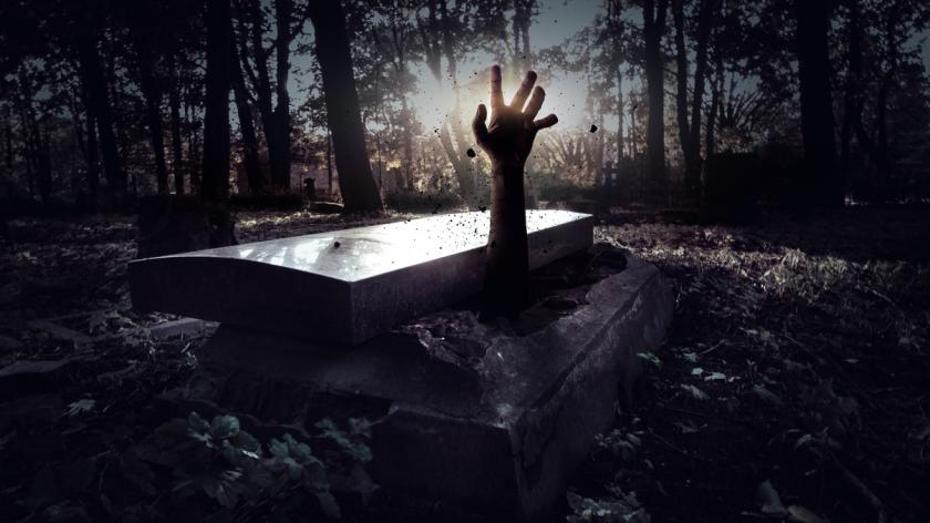 Hand rising out of a grave