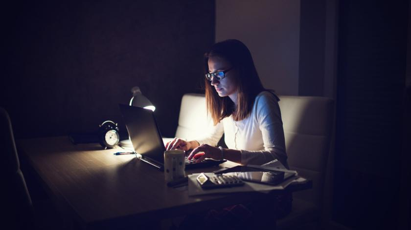 Business woman working late at night to meet an urgent deadline.