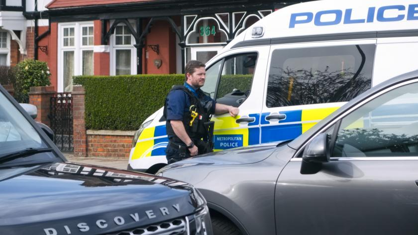 A Metropolitan Police officer standing beside a van at a nearby incident in a suburban street in Greater London.