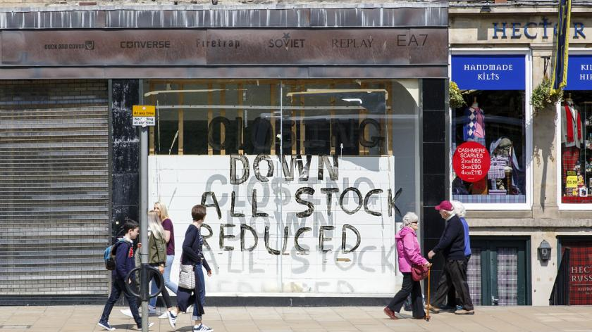 People walk past a shuttered shop