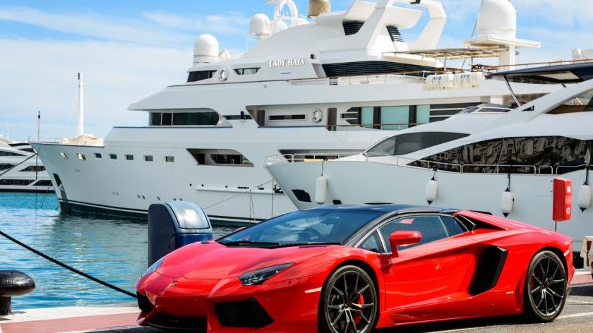 Rich and wealthy: Front view of a red super sport car (Lamborghini) parked alongside luxury yachts moored in the marina of Puerto Jose Banus on the Costa del Sol in Marbella, Spain.