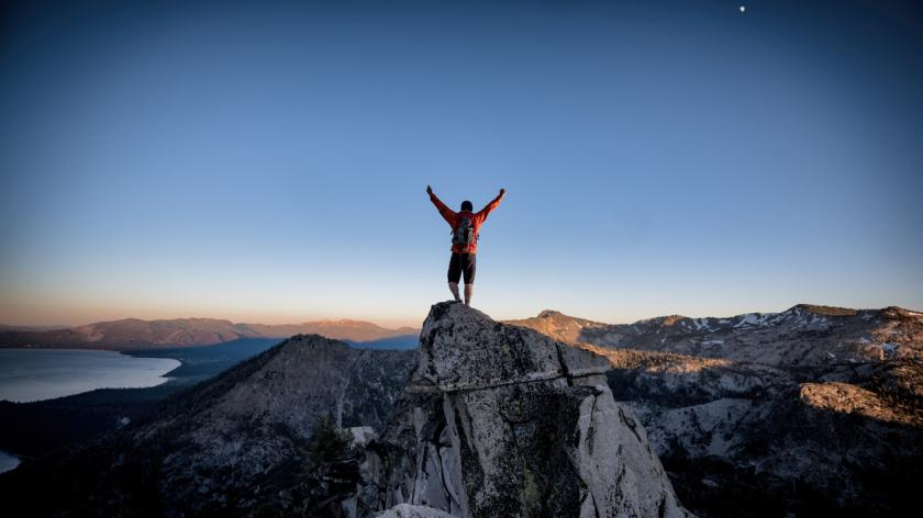 A climber reaches the summit of an exposed mountain