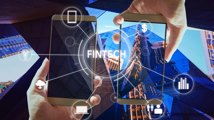 """""""Fintech"""" word on digital virtual screen with two businessman hands holding smartphones background."""