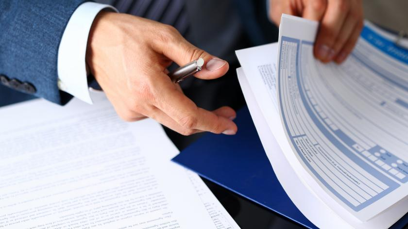 A man in a suit signing an insurance form