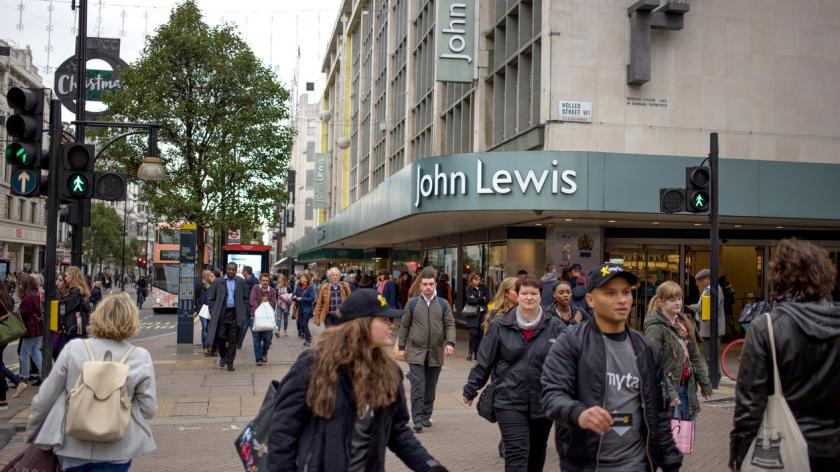 Busy Shoppers in Oxford Street, London, walking past the flagship John Lewis store.