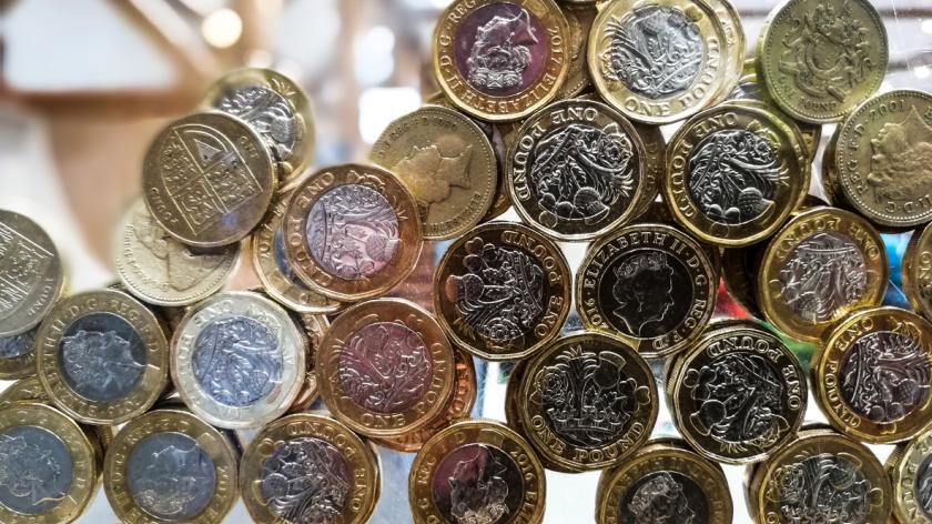 Close up of large collection of donated British pound coins inside charity box
