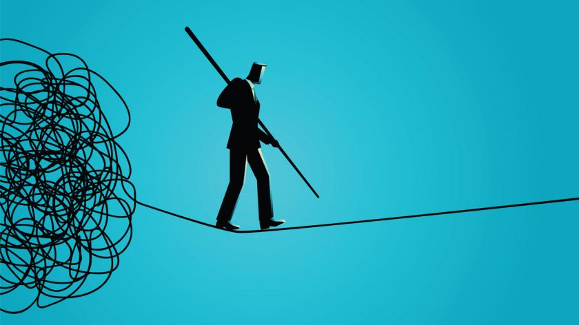 Businessman walking away carefully from tangled rope