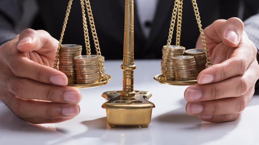 Businessman balancing coins on scales