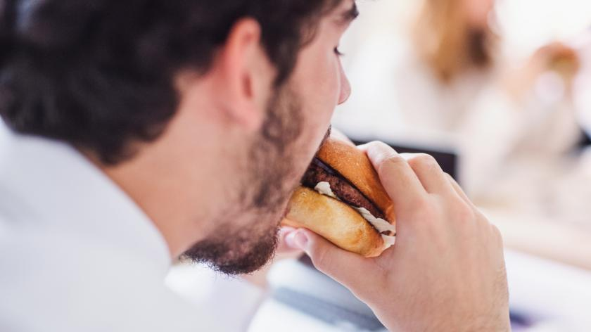 Young man having lunch in an office