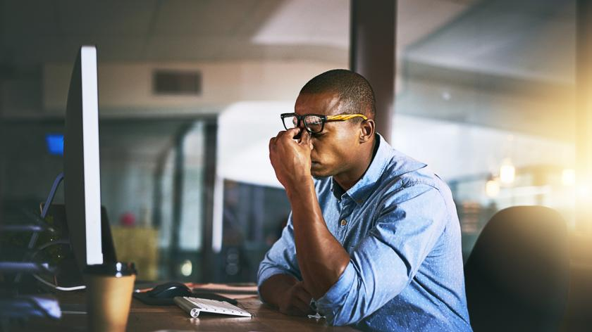 Frustration: Shot of a young businessman experiencing stress during late night at work
