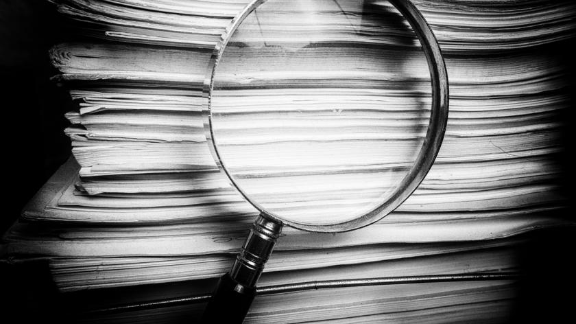 Magnify glass inspects paper documents