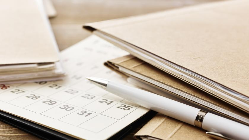 A picture of a pile of papers, paperwork and a calendar