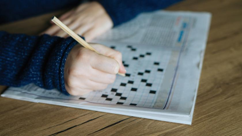hand holding a pencil and solves crossword puzzle