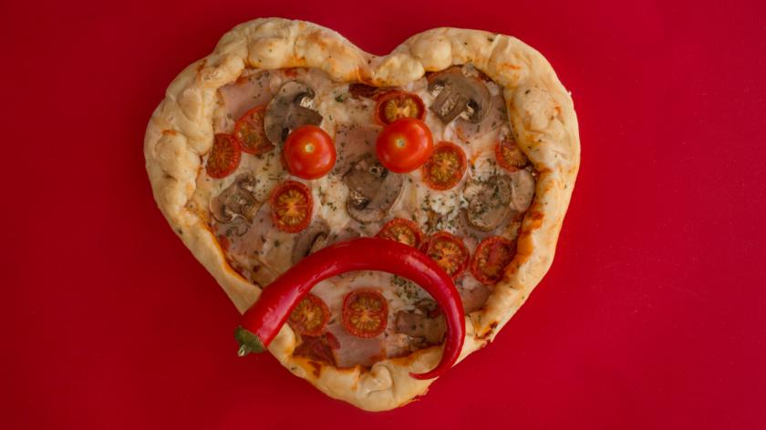 Pizza heart-shaped on red background