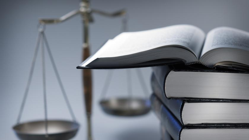 Stack Of Law Books In Front Of Scales Of Justice