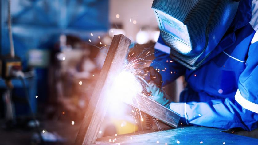 Professional welder in a factory welding steel bars