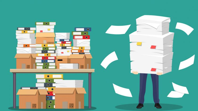 Businessman holds pile of office papers and documents