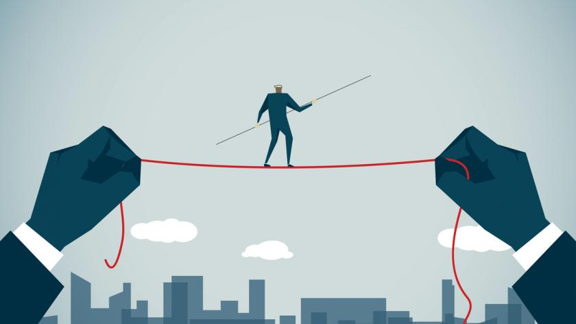 business person walking on tightrope