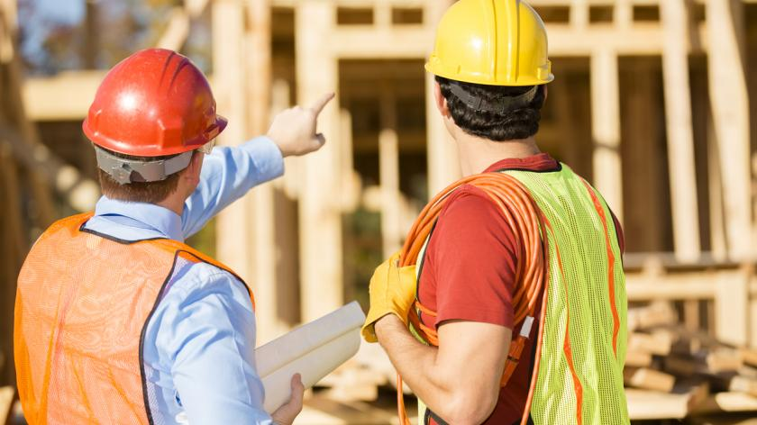Construction worker, supervisor discuss blueprints at work site