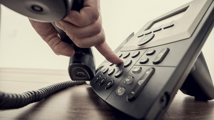 hand holding telephone receiver and dialing a phone number